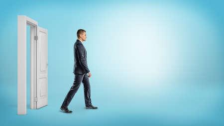 Een zakenman op blauwe achtergrond lopen door een open witte deurframe. Stockfoto