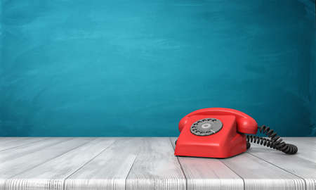 hotline: 3d rendering of a bright red dial phone standing on a wooden desk and a blue wall background. Stock Photo