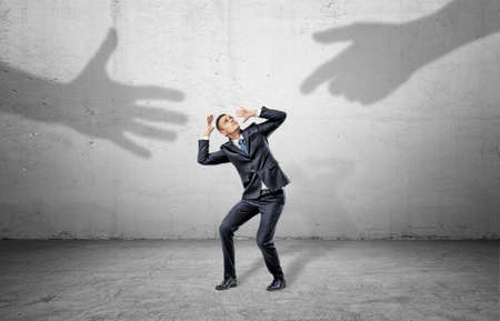 A scared businessman hides from two giant shadows of human hands reaching to him. Stock Photo