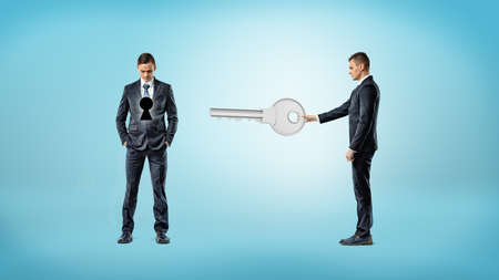 A businessman holds out a giant key in the direction of another man who has a dark keyhole on his torso. Stock Photo