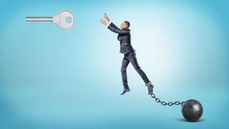 Een zakenman die aan een ijzeren bal is gekoppeld, probeert te springen en een grote zilveren sleutel te bereiken die hierboven hangt. Stockfoto