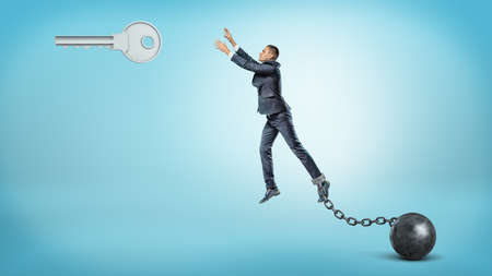 A businessman chained to an iron ball tries to jump and reach a large silver key hanging above.