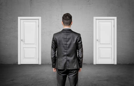 A businessman with his back turned stands between two identical closed white doors. 스톡 콘텐츠