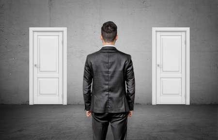 Un hombre de negocios con la espalda vuelta se encuentra entre dos idénticas cerradas puertas blancas.