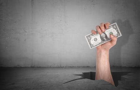 Eine große männliche Hand, die aus einem tiefen gebrochenen Loch in einem Zementboden heraus schlägt, um einen Dollarschein zu fangen. Standard-Bild