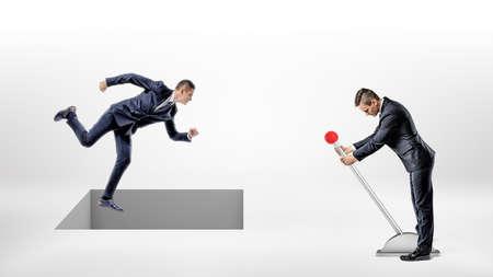 ビジネスマンは白い地面を走り、レバーの男によってコントロールされた四角い穴が彼の足元に開きます。