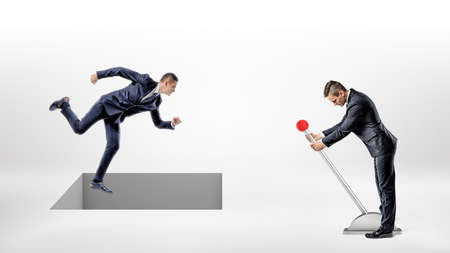 A businessman runs on white ground while a square hole controlled by a man on a lever opens right under his feet.