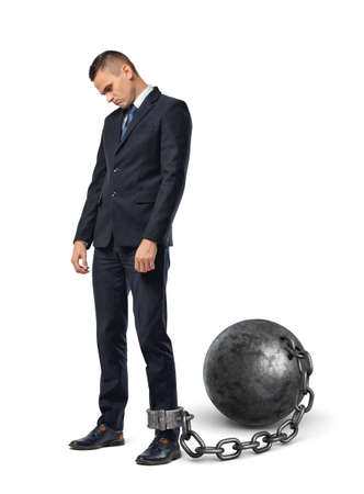 A sad businessman looks down while shackled to a large iron ball with a chain to his ankle. Stock Photo