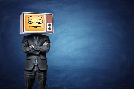 実業家は彼の頭にレトロなテレビを着て、黄色がっかり絵文字を放送します。 写真素材