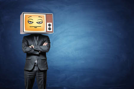 A businessman wears a retro TV on his head and broadcasts a yellow disappointed emoji. Imagens - 86369427