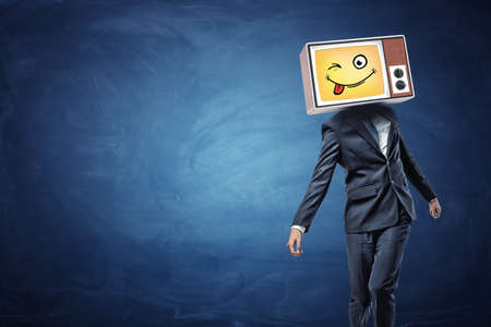A strangely walking businessman wears a vintage TV on his head and projects a yellow emoji with a sticking tongue.