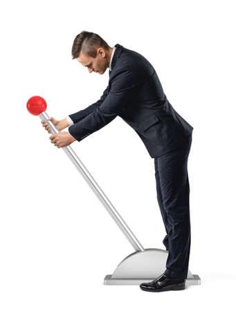 Een zakenman staat bij een grote hendel met een rode ronde knop en begint het te bewegen.