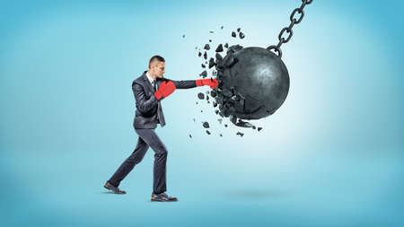 A tiny businessman in red boxing gloves breaks a large swinging wrecking ball in small pieces. Stock Photo