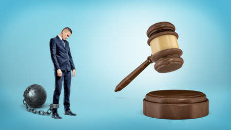 trapped: A small sad businessman leashed to an iron ball stands near a giant hitting judge gavel. Stock Photo