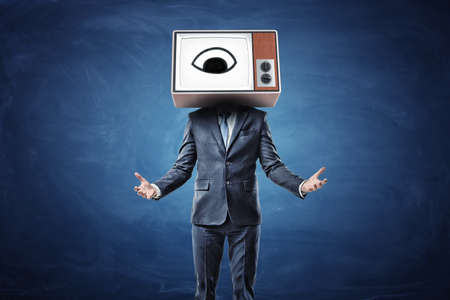 A businessman with both arms in front of him palms up and a head replaces by a TV box with an eye on the screen. Banco de Imagens