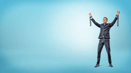 Een gelukkige zakenman staat met handen opgewekt in de overwinningsbeweging om gebroken boeien te tonen.