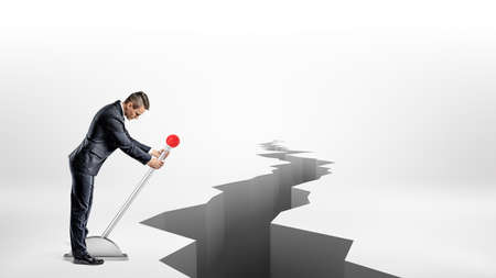 hole: A businessman turns a large metal lever while standing beside a long earthquake rift on white background.