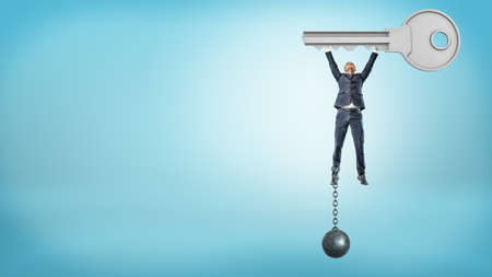 A businessman chained to an iron ball flies upwards while holding a huge metal key. Stockfoto