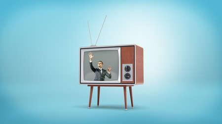 Een zakenman in een retro tv-scherm legt zijn handen plat op het scherm van binnenuit. Stockfoto