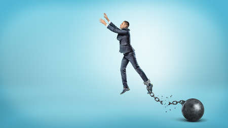 heavy risk: A businessman leaps up with outstretched hands while hes chained to an iron ball with a broken link. Stock Photo