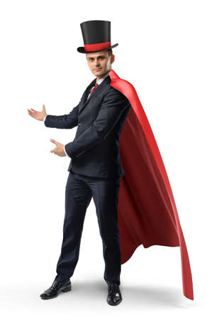 A businessman wearing a red cape and a big illusionists hat shows something on a white background.