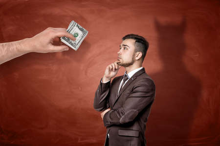 A giant hand with a roll of dollar bills in front of a thinking businessman who cast a shadow of a devil. Stock Photo