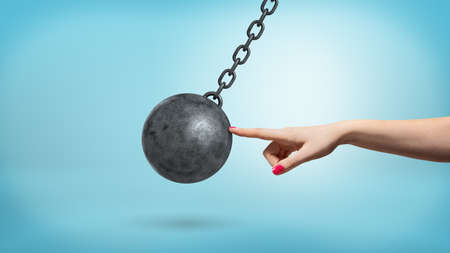 A giant female arm with one finger lightly touching a black iron wrecking ball and stopping its movement.