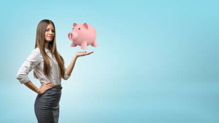 A young businesswoman with long hair stands and holds one palm up with a large piggy bank hovering above it. Stock Photo