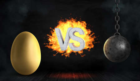 3d rendering of a large concrete letters VS on fire stand between a large golden egg and a black iron wrecking ball.