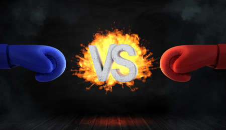 3d rendering of glowing blast with concrete letters VS stands between a red and a blue boxing glove. Фото со стока