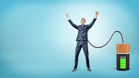 A happy businessman with raised hands is connected to a large battery charging him. Stock Photo