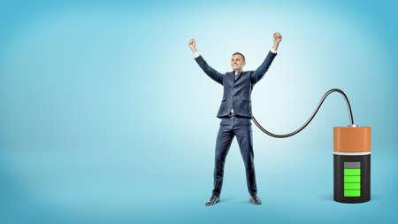 Ein glücklicher Geschäftsmann mit den angehobenen Händen wird an eine große Batterie angeschlossen, die ihn auflädt. Standard-Bild