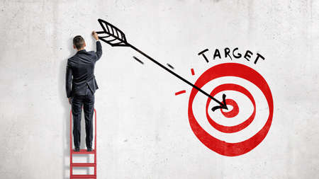 A businessman stands and draws on the wall a big arrow in the center of a red archery target.