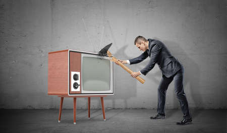 A businessman on concrete background fails to smash an old retro TV set with a broken hammer.