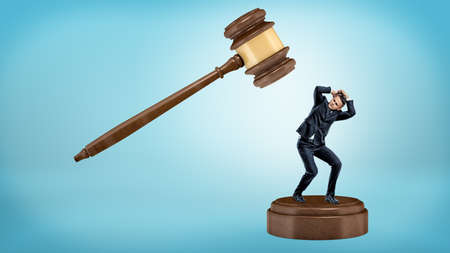 A small businessman tries to avoid a giant gavel strike while standing on a sound block. Stock Photo