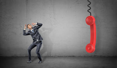 A small scared businessman on concrete background near a large red retro phone handle hanging down.