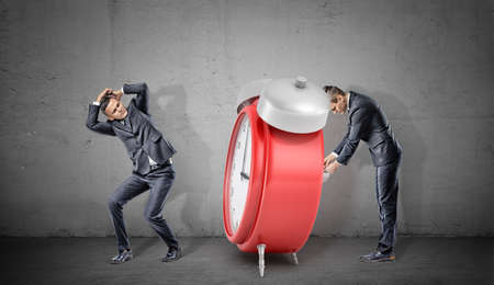 A businessman covers his head form a giant red retro alarm clock being winded up by another businessman.