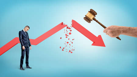 A small sad businessman stands near a red statistic arrow broken by a giant hand holding a judge gavel.