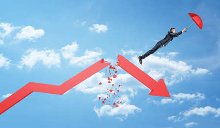 A small businessman holds a red umbrella and flies away from a large red statistic arrow broken in half.