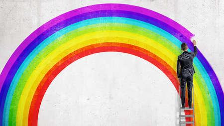 ビジネスマンは階段の上に立ち、虹の壁の絵の中に最後のカラフルな線を描きます。