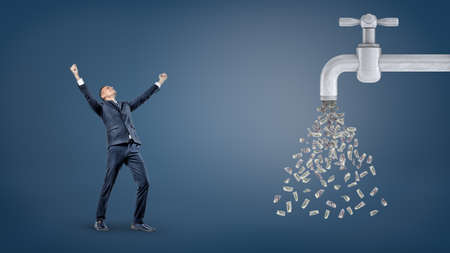 Mały, zwycięski biznesmen stoi z podniesionymi rękami w pobliżu gigantycznego kranu z wodą, z którego wycieka wiele dolarowych banknotów.