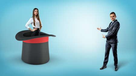Un hombre de negocios muestra una empresaria segura de sí misma de pie dentro de un sombrero de ilusionistas gigantes sobre un fondo azul.