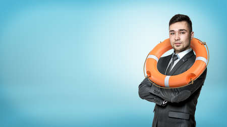 A businessman in a front view with hands crossed and an orange life buoy hanging on his neck. Stock Photo