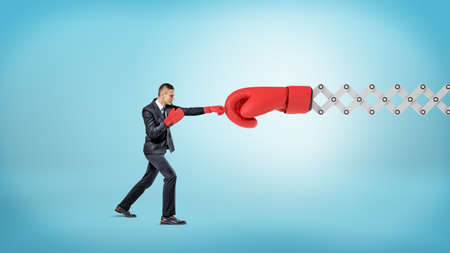 A small businessman in sport gloves punches a giant red boxing glove on a metal scissor arm.