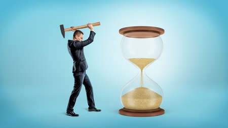 A businessman holds a large heavy hammer ready to hit a large hourglass with half of its sand fallen down.