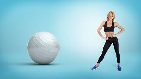A young fit blonde woman stands with hands on her hips near a large silver exercise ball. Stock Photo