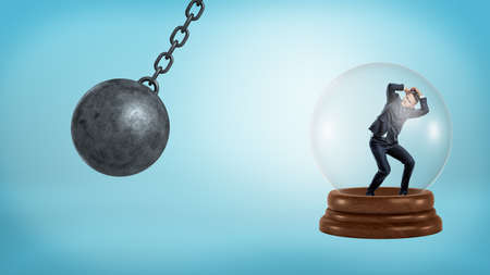 A small businessman stands inside a glass sphere with a swinging wrecking ball threatening him.