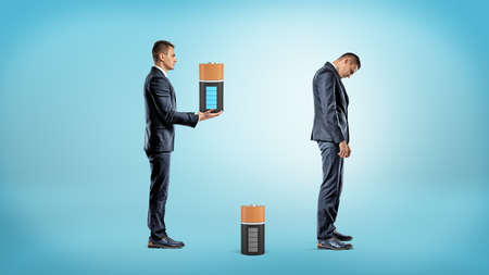 A businessman brings a large fully charged battery to replace a depleted one from inside a very tired businessman. Stock Photo