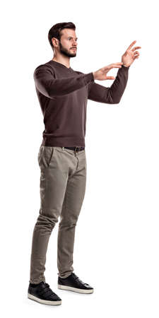A young man in fashionable casual closes stands on a white background with hands as if pressing invisible buttons. Reklamní fotografie