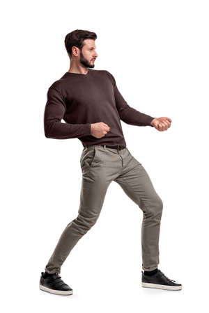 A bearded man a jumper and pants tries to pull a strong invisible rope on a white background.